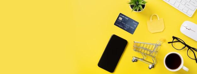 Vista superior do conceito de compras online com cartão de crédito, telefone inteligente e computador isolado no fundo da mesa amarela do escritório.