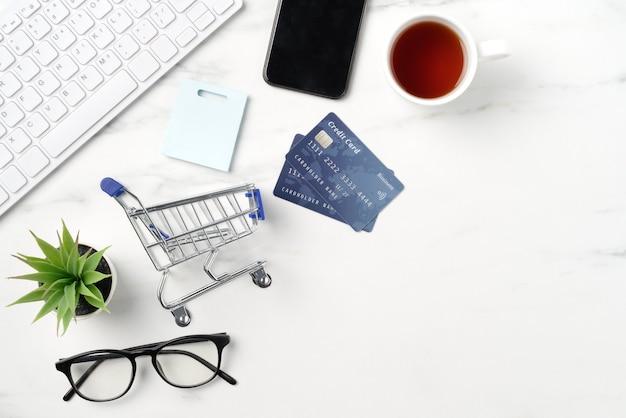 Vista superior do conceito de compras online com cartão de crédito, telefone inteligente e computador isolado no fundo de mesa de mármore branco de escritório.