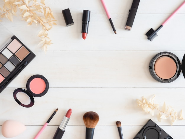 Vista superior do conceito de cosméticos com batom, produtos de maquiagem, paleta da sombra, pó no fundo da tabela de cor branca.