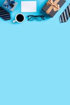 Vista superior do conceito de design da ideia do presente do dia dos pais com uma maquete em branco branca sobre fundo azul de mesa de saudação.