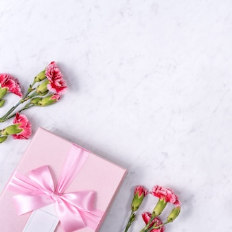 Vista superior do conceito de design de plano de fundo do dia das mães com buquê de flores de cravo na mesa de mármore