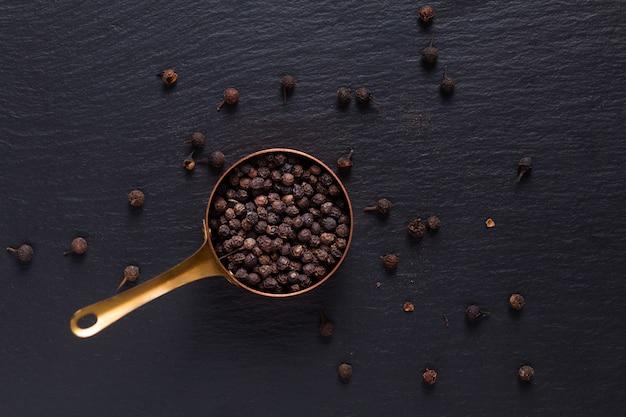 Vista superior do conceito de especiarias alimentares de pimenta preta orgânica em copo de cobre em pedra de ardósia preta com espaço de cópia
