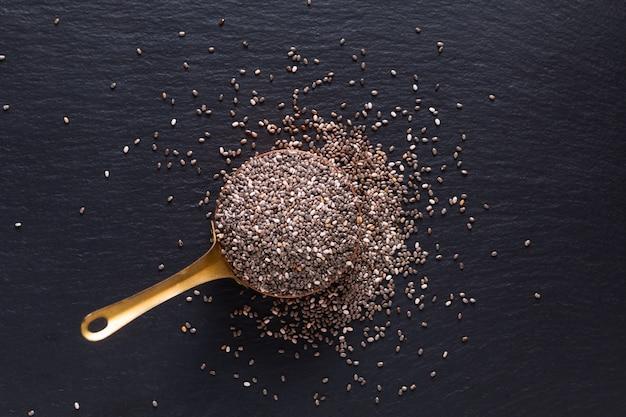 Vista superior do conceito de especiarias alimentares de semente de chia orgânica em copo de cobre em pedra ardósia preta com espaço de cópia