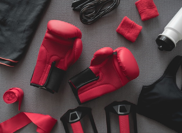 Vista superior do conceito de ginásio de boxe com luva de boxe, roupa de ginástica, pular corda e acessórios em fundo de esteira de ioga.