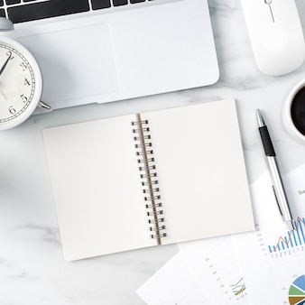 Vista superior do conceito de trabalho de mesa de escritório com caderno em branco, relatório, despertador