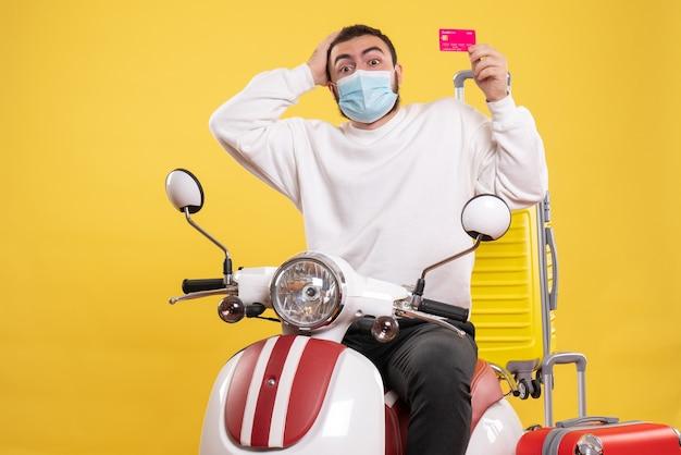 Vista superior do conceito de viagem com cara confuso com máscara médica sentado na motocicleta com mala amarela e segurando o cartão do banco
