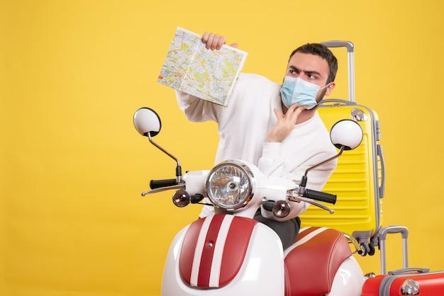 Vista superior do conceito de viagem com um cara confuso com uma máscara médica em pé perto da motocicleta com uma mala amarela e segurando
