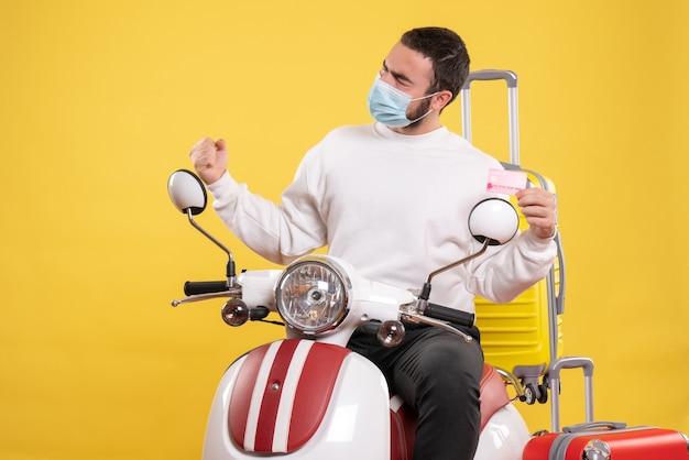 Vista superior do conceito de viagem com um cara orgulhoso com máscara médica sentado na motocicleta com uma mala amarela e segurando o cartão do banco