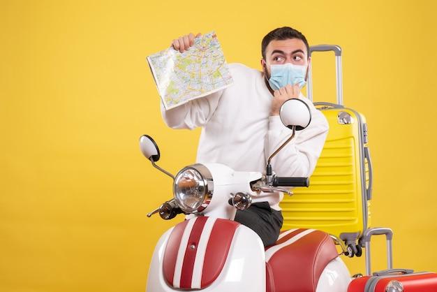 Vista superior do conceito de viagem com um jovem com máscara médica em pé perto de uma motocicleta