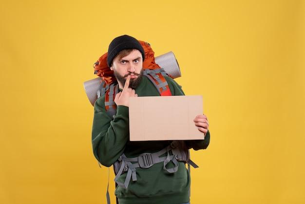 Vista superior do conceito de viagens com o jovem pensativo com packpack e segurando espaço livre para escrever
