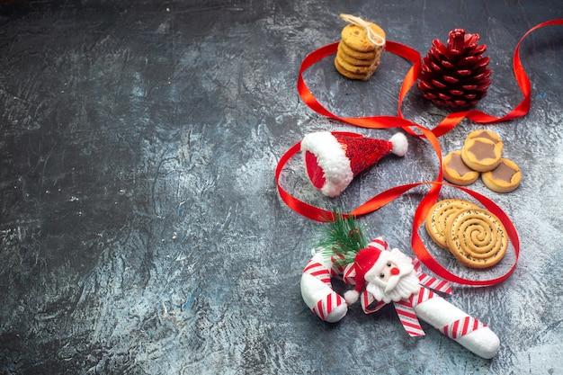 Vista superior do cone de conífera vermelha do chapéu de papai noel e vários biscoitos biscoitos no lado esquerdo na superfície escura