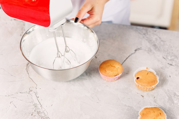 Vista superior do confeiteiro feminino mistura um creme branco em uma placa de metal profunda com misturador de cozinha vermelho para cupcakes recém-assados.