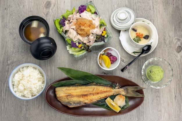 Vista superior do conjunto de alimentos japoneses, peixe frito, servir com arroz cozido no vapor e salada de carne de porco yum