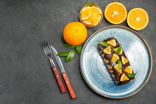 Vista superior do conjunto de bolos saborosos inteiros e cortados de laranjas amarelos na mesa escura