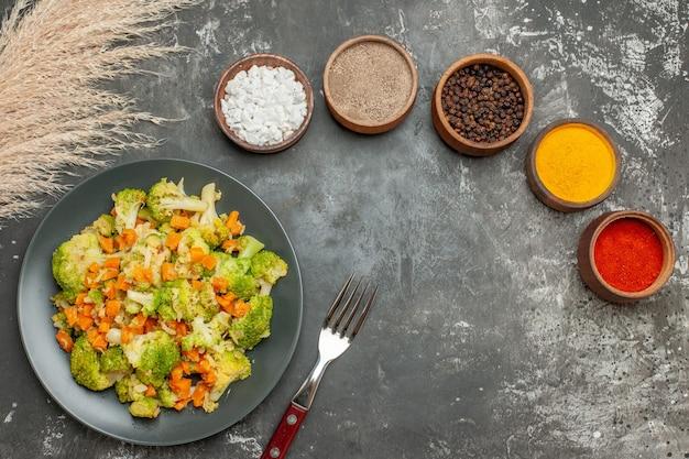 Vista superior do conjunto de diferentes especiarias em tigelas marrons e salada de legumes com brócolis fresco