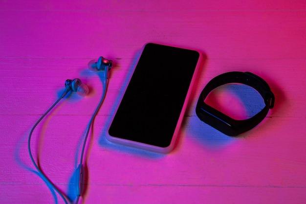 Vista superior do conjunto de dispositivos em luz de néon roxa e fundo rosa. smartphone e smartwatch, fones de ouvido. copyspace para sua publicidade. tecnologia, moderna, gadgets.