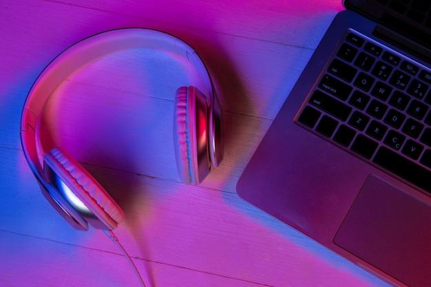 Vista superior do conjunto de dispositivos em luz de néon roxa e fundo rosa. teclado do laptop, fones de ouvido e smartphone com tela preta. copyspace para sua publicidade. tecnologia, moderna, gadgets.