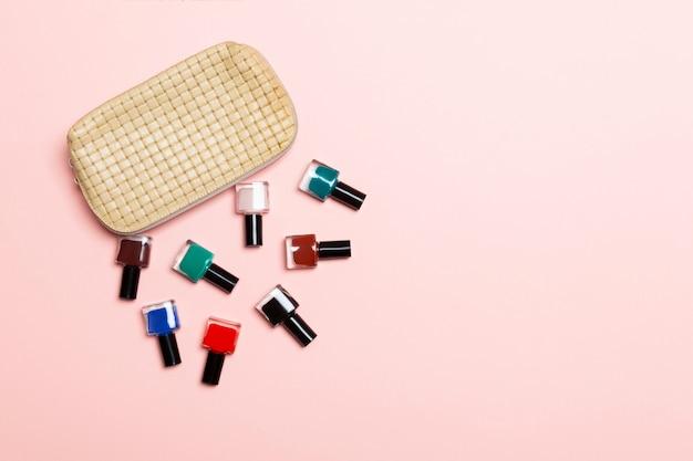 Vista superior do conjunto de esmaltes e vernizes de gel brilhantes, caídos no saco de cosméticos com espaço de cópia no fundo rosa. conceito moderno de unhas Foto Premium