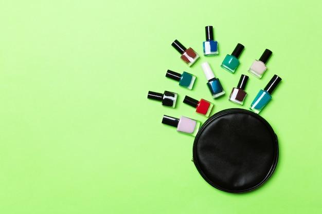 Vista superior do conjunto de esmaltes e vernizes de gel brilhantes, caídos no saco de cosméticos com espaço de cópia sobre fundo verde.