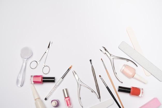 Vista superior do conjunto de ferramentas de manicure para cuidar das unhas sobre uma superfície clara - escova, tesoura, esmalte, lima e pinça Foto Premium