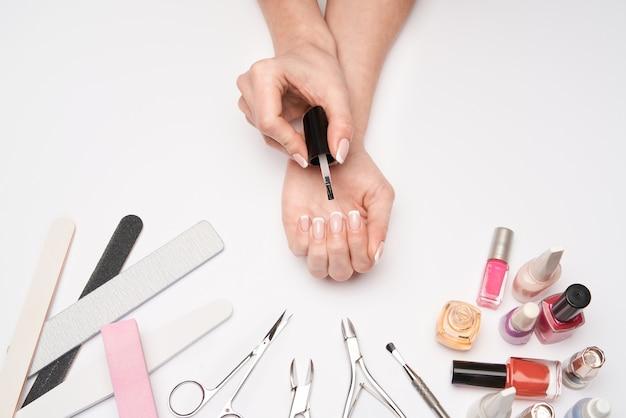 Vista superior do conjunto de ferramentas de manicure para cuidar das unhas sobre uma superfície clara - escova, tesoura, esmalte, lima e pinça