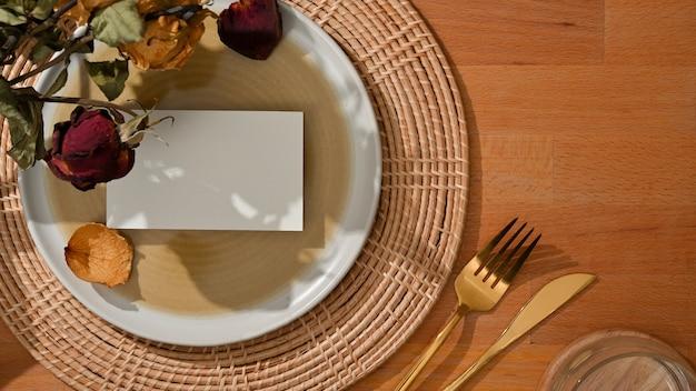 Vista superior do conjunto de jantar com cartão de visita simulado no prato e garfo de latão, faca de mesa e flor decorada na mesa
