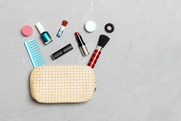 Vista superior do conjunto de produtos de maquiagem e cuidados com a pele, derramando fora da bolsa de cosméticos em fundo de cimento