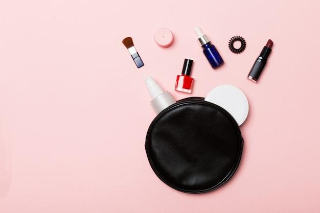 Vista superior do conjunto de produtos de maquiagem e cuidados com a pele, derramando fora da bolsa de cosméticos