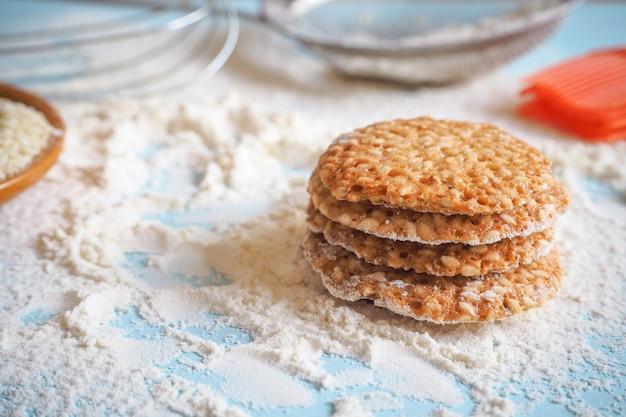 Vista superior do conjunto de produtos para cozinhar biscoitos, utensílios de cozinha e vários biscoitos redondos com gergelim.