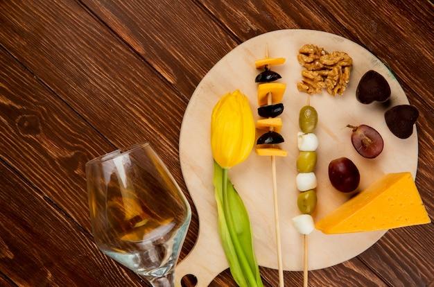 Vista superior do conjunto de queijo como queijo cheddar e parmesão com azeitona noz uva e flor na tábua e copo vazio em fundo de madeira
