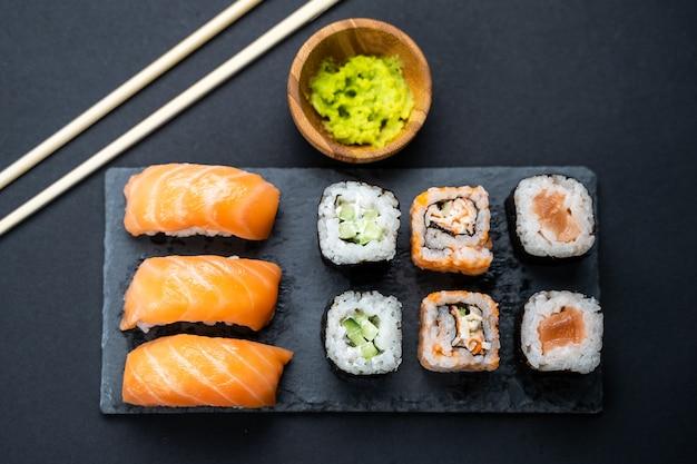 Vista superior do conjunto de rolos de sushi, maki, uramaki, nigiri e sashimi servido na ardósia de pedra.