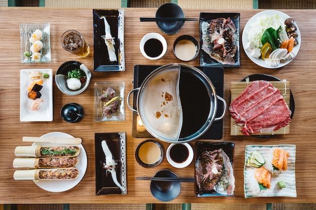 Vista superior do conjunto de shabu incluindo fatias raras wagyu a5 carne, base de shabu, salmão, sushi e legumes