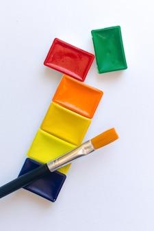 Vista superior do conjunto de tintas aquarela e pincel para pintura de cor de água