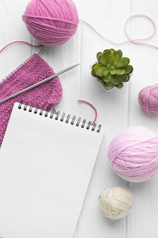 Vista superior do conjunto de tricô com caderno e fios