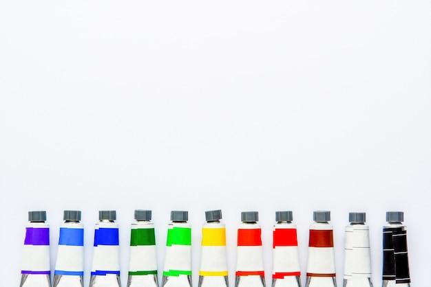 Vista superior do conjunto de tubos coloridos em bloco de desenho branco