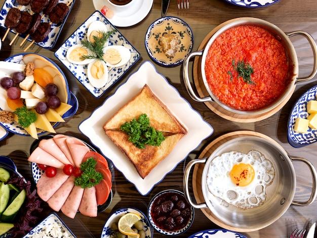 Vista superior do conjunto de vários pratos de comida no café da manhã ovos fritos com tomate salada de frutas presunto legumes torradas de queijo