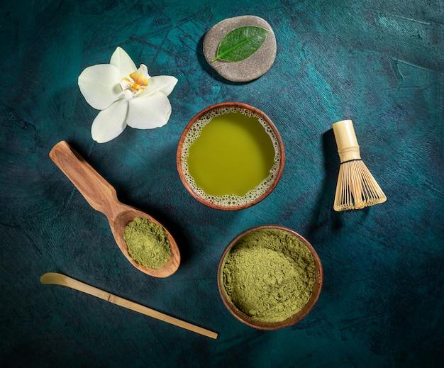 Vista superior do conjunto para cozinhar chá matcha no fundo esmeralda. Foto Premium
