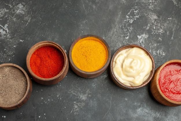 Vista superior do conjunto para molhos contendo diferentes especiarias, maionese e ketchup em fundo cinza