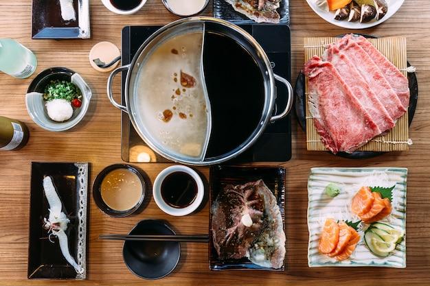 Vista superior do conjunto shabu incluindo fatias raras de carne wagyu a5, shoyu shabu e base clara.