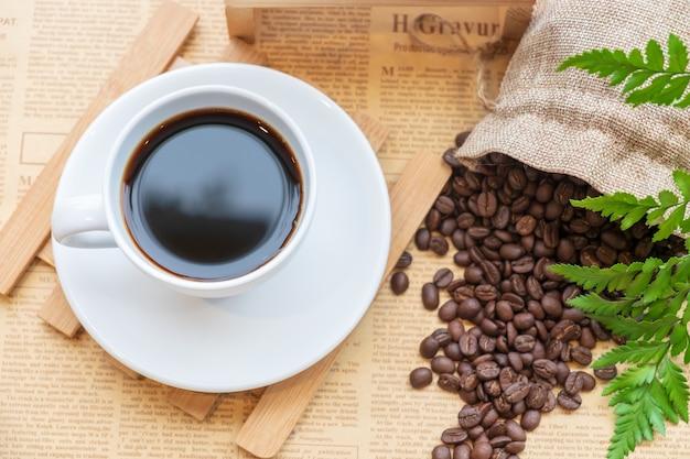 Vista superior do copo branco de café preto na placa de madeira sobre o feijão de café turva