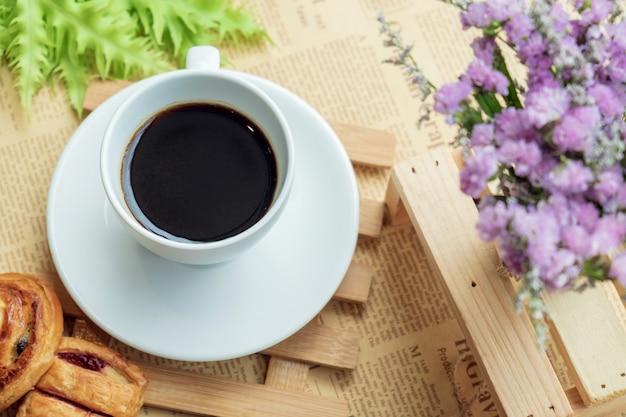 Vista superior do copo branco do café preto ou chá na placa de madeira sobre o feijão de café borrado com