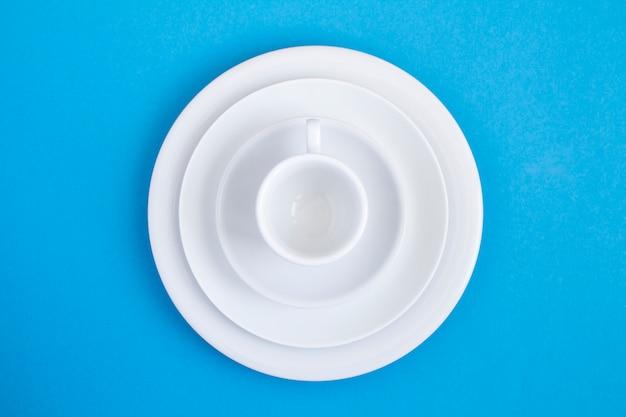 Vista superior do copo branco vazio e pratos em azul