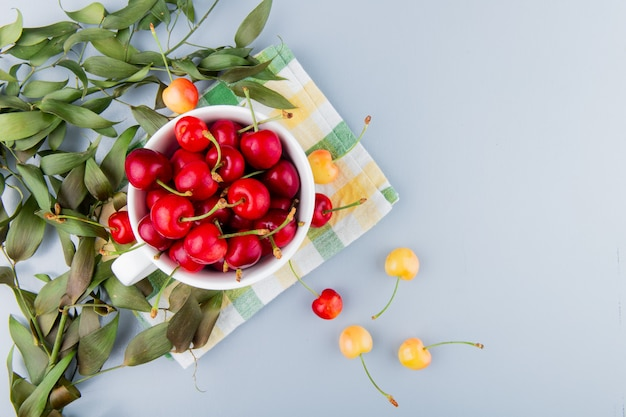 Vista superior do copo cheio de cerejas vermelhas no lado esquerdo e superfície branca decorada com folhas com espaço de cópia