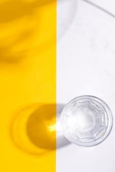 Vista superior do copo de água fria fresca em uma superfície duotônica