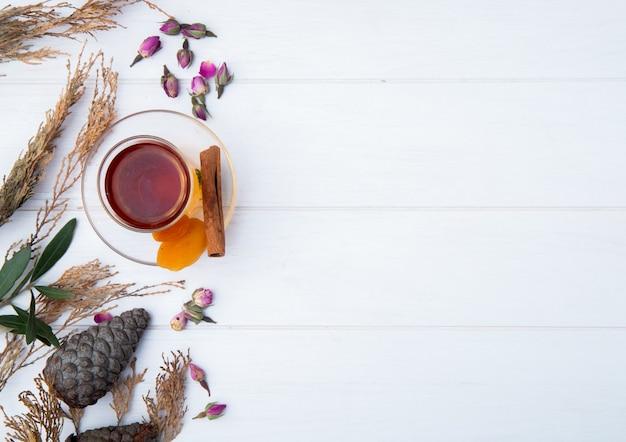Vista superior do copo de armudu de chá com damascos secos, pau de canela e botões de rosa secos espalhados em branco, com espaço de cópia