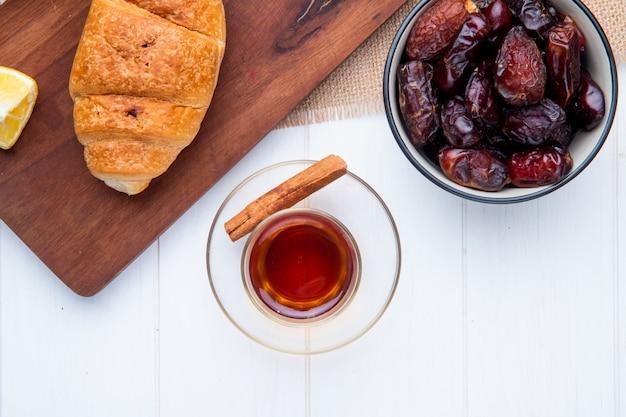 Vista superior do copo de armudu de chá com tâmaras secas doces em uma tigela e croissant em uma tábua de madeira em branco