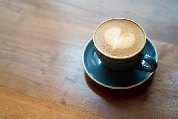Vista superior do copo de café quente com uma espuma do coração da arte do barista na tabela de madeira.