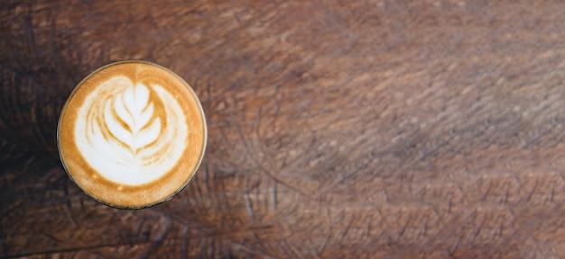 Vista superior do copo de café quente de cappuccino na bandeja de madeira com latte art na mesa de madeira