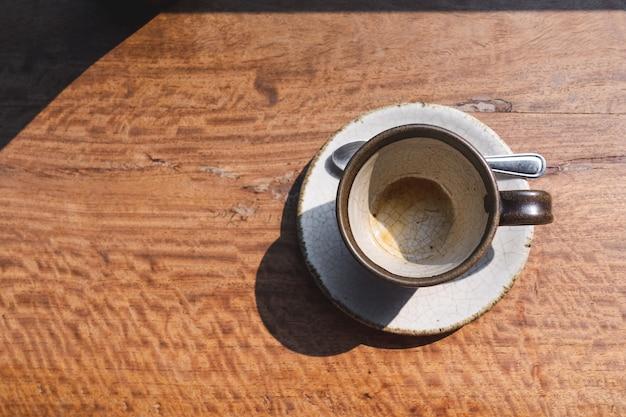 Vista superior do copo de cerâmica vazio café na mesa de madeira com luz da manhã