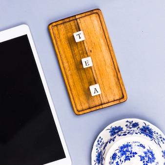 Vista superior do copo de chá com carta corta e tablet
